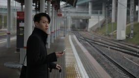 El hombre coreano con el teléfono se está colocando en el ferrocarril al aire libre almacen de video
