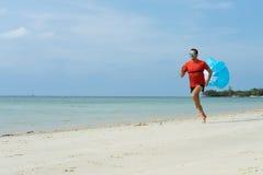 El hombre corre, corre en la playa, en los deportes tropicales de los juegos del país, con atado funcionando con un paracaídas de Imagenes de archivo