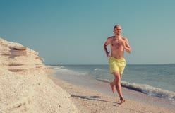 El hombre corre en la línea de la resaca del mar descalzo Imagen de archivo libre de regalías