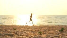 El hombre corre en la playa en el amanecer en la cámara lenta almacen de metraje de vídeo