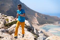 El hombre corre en rocas contra un mar azul Imagenes de archivo