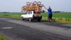 El hombre corre para el coche para el cual transporta los muebles hechos a mano del whiker para persuadir al almadiero del  de Ñ almacen de video