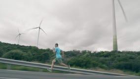 El hombre corre rápidamente a lo largo del camino contra los generadores de viento de funcionamiento metrajes