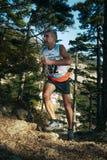 El hombre, corredor de mediana edad funciona con la distancia del rastro del bosque de la raza de piedras Foto de archivo libre de regalías