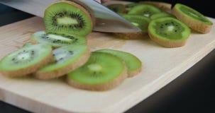 El hombre cortó con un cuchillo una fruta de kiwi almacen de video