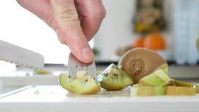 El hombre cortó con un cuchillo una fruta de kiwi dulce y jugosa fresca en muchas rebanadas almacen de video