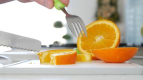 El hombre cortó para una fruta de la naranja de la ensalada una en rebanadas dulces y condimentadas frescas metrajes