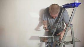 El hombre corta el espejo con un cortador de cristal metrajes