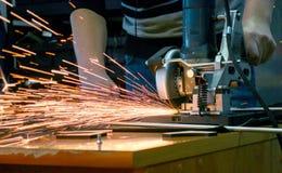 El hombre corta el metal y chispea Imagen de archivo libre de regalías