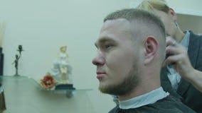 El hombre corta el pelo en un salón de belleza metrajes