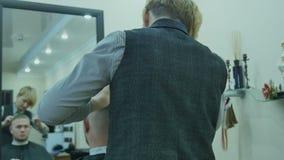 El hombre corta el pelo en un salón de belleza almacen de video