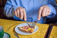 El hombre corta la pizza con queso y el jamón imagen de archivo libre de regalías