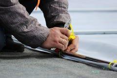 El hombre corta los lazos plásticos de las abrazaderas con los alicates de los cortaalambres durante desmontar de la etapa despué Fotografía de archivo libre de regalías