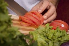 El hombre corta los tomates Imágenes de archivo libres de regalías