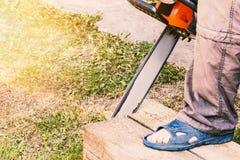 El hombre corta una madera del pino con una motosierra foto de archivo libre de regalías