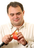 El hombre corta una manzana Imágenes de archivo libres de regalías