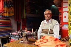 El hombre cose la ropa en la máquina de coser en su taller en el mercado local cerca del Har Ki Pauri en Haridwar fotografía de archivo libre de regalías