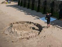 El hombre crea la escultura de la arena de la cara grande en el banco del sur del Támesis Ri fotos de archivo