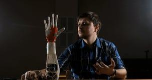 El hombre crea el movimiento para el brazo plástico mecánico Brazo robótico cibernético Movimiento del brazo de los robots Futuri