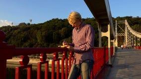 El hombre creativo coloca y pone sus ideas abajo en un puente del río en la puesta del sol almacen de video