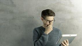 El hombre creativo del inconformista listo piensa que ipad digital de la tableta del tacto consigue una idea, que salta para arri