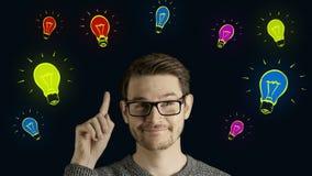 El hombre creativo listo piensa consigue una idea, que salta para arriba como lámparas coloreadas simbólicas de la forma de la an almacen de video