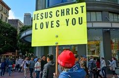 El hombre cristiano lleva a cabo una muestra de Jesus Christ Love You durante los protes Fotos de archivo