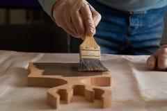El hombre cubre a una tajadera con aceite especial en el pasillo de la producción fotos de archivo libres de regalías
