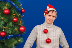 El hombre cuesta cerca de un árbol elegante del Año Nuevo que se viste en hola Fotografía de archivo libre de regalías