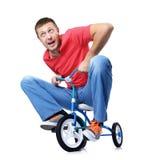 El hombre curioso en una bicicleta de los niños Fotos de archivo libres de regalías
