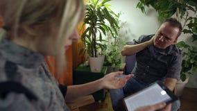 El hombre daña el cuello mientras que usando gafas de la realidad virtual la mujer leyó en la tableta almacen de metraje de vídeo