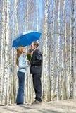 El hombre da el ramo de la muchacha bajo el paraguas Imagenes de archivo