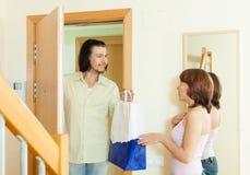 El hombre da el regalo a la mujer en casa fotos de archivo