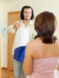 El hombre da el regalo a las mujeres en casa imagenes de archivo