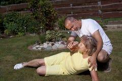 El hombre da a mujer con el agotamiento de calor algo beber Foto de archivo libre de regalías