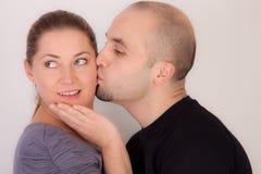 El hombre da a mujer un beso Foto de archivo libre de regalías