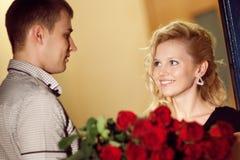 El hombre da rosas a una muchacha foto de archivo