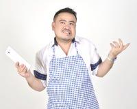 El hombre de Asian del comerciante en el delantal blanco y azul está sintiendo pesar o el taladro cuando consiga las malas notici imágenes de archivo libres de regalías