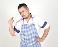 El hombre de Asian del comerciante en el delantal blanco y azul está sintiendo pesar o el taladro cuando consiga las malas notici imagen de archivo libre de regalías