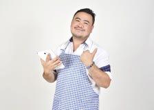 El hombre de Asian del comerciante en el delantal blanco y azul está sintiendo sorprendido o excitado cuando consiga las buenas n fotografía de archivo