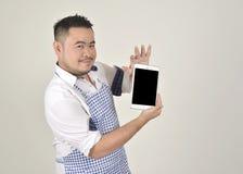 El hombre de Asian del comerciante en el delantal blanco y azul está sintiendo sorprendido o excitado cuando consiga las buenas n imagen de archivo