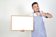 El hombre de Asian del comerciante en el delantal blanco y azul a sostener amplio blanco en blanco para puso un poco de texto o l fotos de archivo libres de regalías