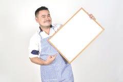 El hombre de Asian del comerciante en el delantal blanco y azul a sostener amplio blanco en blanco para puso un poco de texto o l Foto de archivo libre de regalías