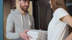 El hombre de entrega feliz de la pizza visita el hogar con las cajas a un cliente Dando el dinero al trabajador y mostrando los p metrajes