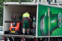 El hombre de entrega que descargaba las mercancías de Heineken del camión de reparto de consumición parqueó en la calle cerca de  imagen de archivo libre de regalías