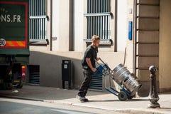 El hombre de entrega que descargaba mercancías del camión de reparto de consumición parqueó en la calle cerca de hotel de parque imagen de archivo libre de regalías