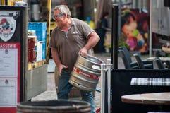 El hombre de entrega que descargaba mercancías del camión de reparto de consumición parqueó en la calle cerca de restaurante fotografía de archivo