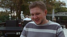 el hombre de 4K A hace una orden en una parte exterior de un café dando vuelta a las páginas del menú metrajes