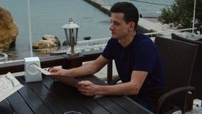 el hombre de 4K A se sienta al aire libre en un café y lee un menú almacen de video