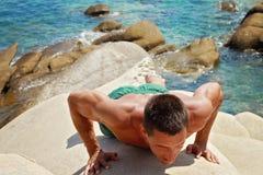 El hombre de la aptitud del entrenamiento que hace el tablón empuja hacia arriba ejercicio al aire libre contra el mar Fotos de archivo libres de regalías